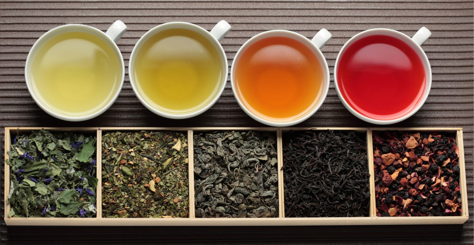 Black , green , fruit tea cups and assortment of dry tea leaves in boxes